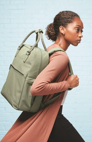 A model in an orange sweater carries an olive backpack